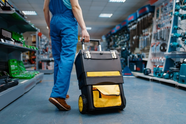 Il lavoratore di sesso maschile in uniforme tiene la cassetta degli attrezzi su ruote nel negozio di attrezzi. scelta di attrezzature professionali in ferramenta, supermercato di strumenti