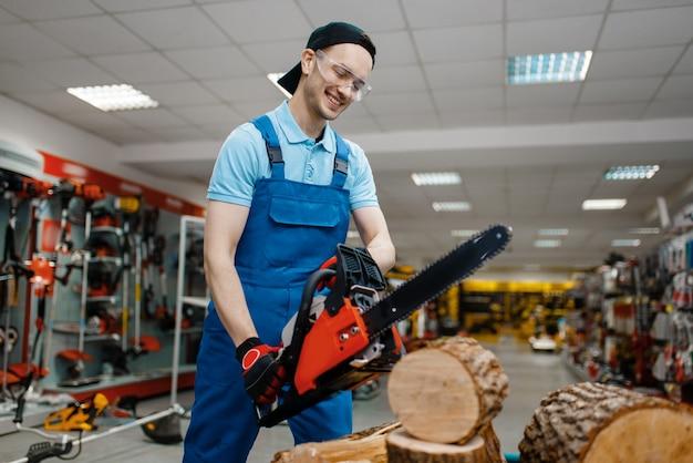 Lavoratore di sesso maschile in motosega di prova uniforme nel negozio di utensili. scelta di attrezzature professionali nel negozio di ferramenta, supermercato di strumenti elettrici