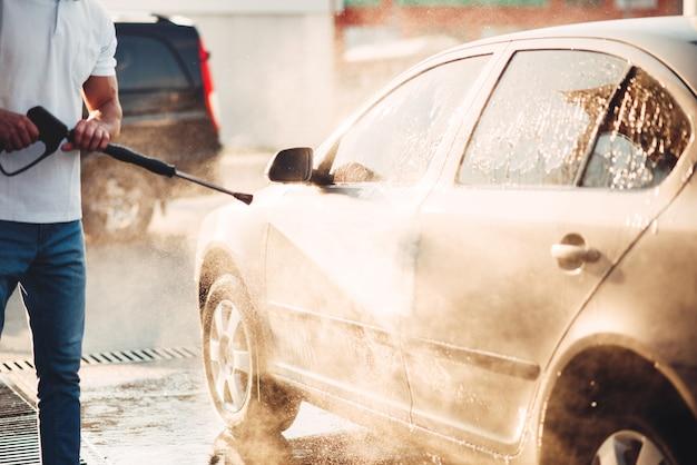 Lavoratore di sesso maschile lavare l'auto con idropulitrice. stazione di lavaggio auto