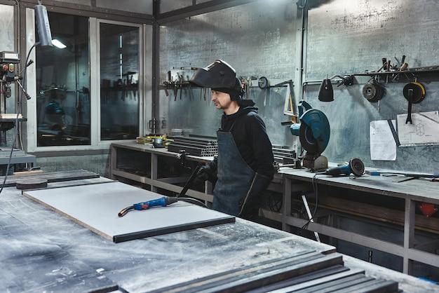Il lavoratore maschio che indossa casco e guanti sta per saldare la costruzione in acciaio in fabbrica