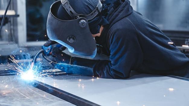 Lavoratore di sesso maschile che indossa casco e guanti per saldare la costruzione in acciaio in fabbrica