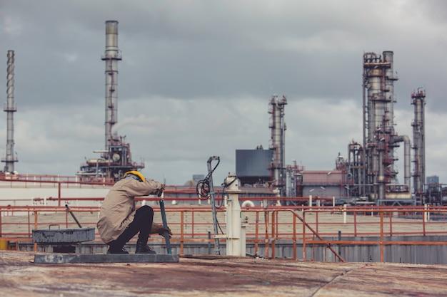 Lavoratore di sesso maschile che indossa indumenti protettivi che pulisce la costruzione industriale del serbatoio di stoccaggio dell'olio del tetto