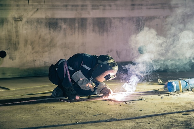 Lavoratore maschio che indossa indumenti protettivi riparazione piastra inferiore serbatoio di stoccaggio costruzione industriale riflettore fumo all'interno di spazi ristretti.