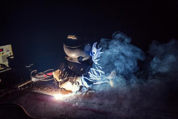 Lavoratore maschio che indossa indumenti protettivi riparazione piastra inferiore serbatoio olio costruzione industriale fumo all'interno di spazi ristretti.