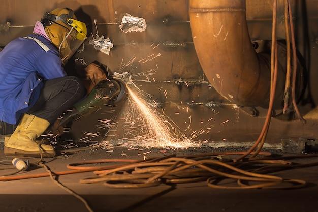 Lavoratore di sesso maschile che indossa indumenti protettivi e ripara macinazione di petrolio e gas da costruzione industriale o serbatoio di stoccaggio all'interno di spazi ristretti.