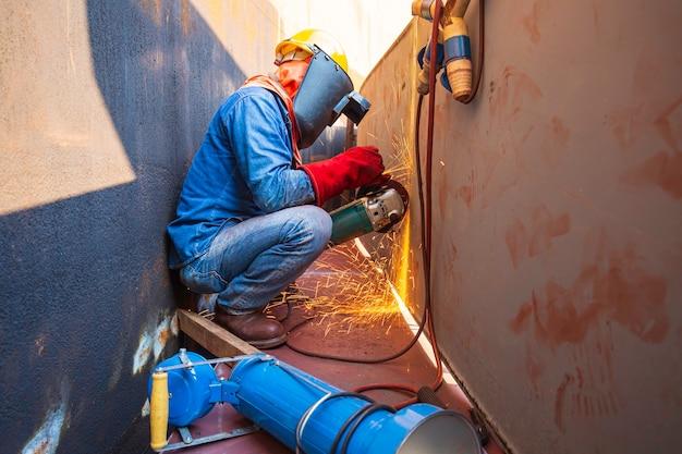 Lavoratore di sesso maschile che indossa indumenti protettivi e ripara la piastra inferiore del serbatoio di stoccaggio della macinazione all'interno di spazi ristretti