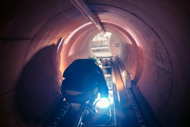 Lavoratore di sesso maschile che indossa indumenti protettivi e ripara saldatura di petrolio e gas da costruzione industriale o serbatoio di stoccaggio orizzontale all'interno di spazi ristretti.
