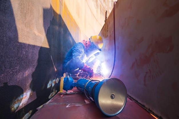 Lavoratore di sesso maschile che indossa indumenti protettivi e ripara saldatura di petrolio e gas da costruzione industriale o serbatoio di stoccaggio all'interno di