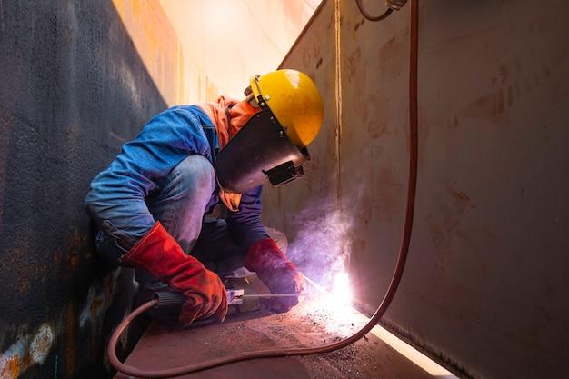 Lavoratore di sesso maschile che indossa indumenti protettivi e ripara saldatura industriale di petrolio e gas o serbatoio di stoccaggio all'interno di spazi ristretti