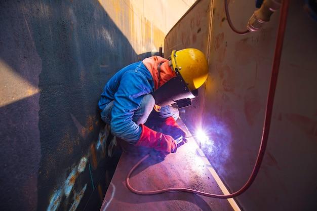 Lavoratore di sesso maschile che indossa indumenti protettivi e ripara saldatura di petrolio e gas da costruzione industriale o serbatoio di stoccaggio all'interno di spazi ristretti.