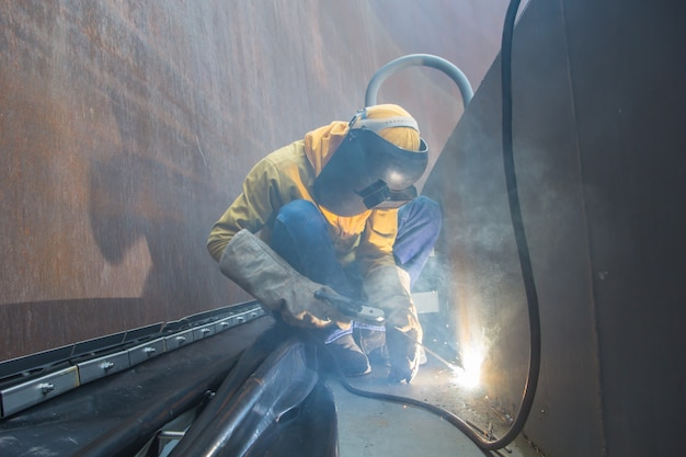 Lavoratore di sesso maschile che indossa indumenti protettivi e ripara saldatura di petrolio e gas da costruzione industriale o serbatoio di stoccaggio all'interno di spazi confinati al fumo.