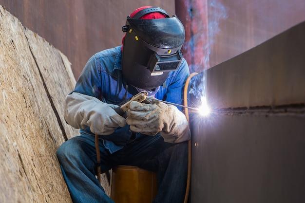 Lavoratore di sesso maschile che indossa indumenti protettivi e ripara la piastra di rivestimento per saldatura industriale petrolio e gas o serbatoio di stoccaggio all'interno di spazi ristretti