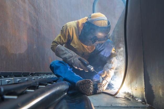 Lavoratore di sesso maschile che indossa indumenti protettivi e ripara la piastra di saldatura per costruzioni industriali petrolio e gas o serbatoio di stoccaggio all'interno di spazi ristretti