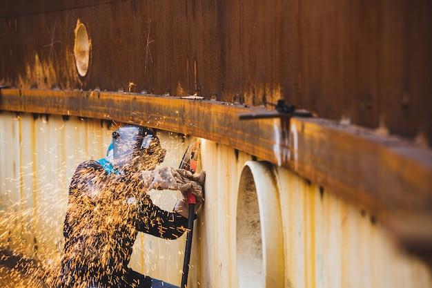 Lavoratore di sesso maschile che indossa indumenti protettivi e ripara saldatura scintilla shell piastra costruzione industriale petrolio e gas o serbatoio di stoccaggio all'interno di spazi ristretti.