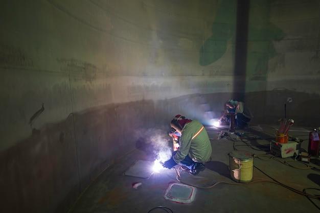 Il lavoratore di sesso maschile che indossa indumenti protettivi e ripara le scintille di saldatura della costruzione industriale della bobina del serbatoio dell'olio pesante all'interno di spazi ristretti.