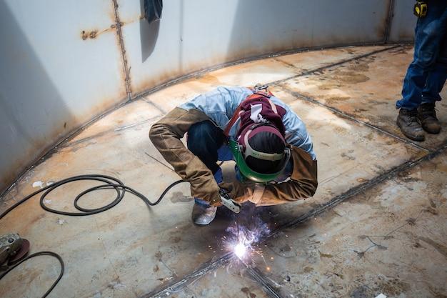 Lavoratore di sesso maschile che indossa indumenti protettivi e ripara il serbatoio di stoccaggio della piastra inferiore del serbatoio di saldatura all'interno di spazi ristretti.