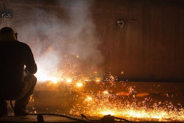 Lavoratore di sesso maschile che indossa indumenti protettivi e ripara il fuoco e il fumo di stoccaggio della piastra del serbatoio di saldatura in spazi ristretti