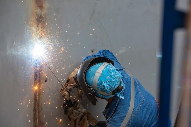 Lavoratore di sesso maschile che indossa indumenti protettivi e ripara il serbatoio di stoccaggio della piastra del guscio del serbatoio di saldatura all'interno di spazi ristretti.