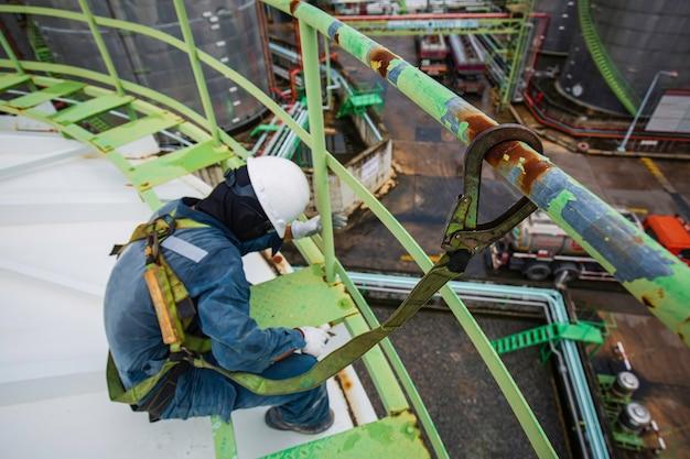Lavoratore di sesso maschile che indossa la prima imbracatura di sicurezza e solitario di sicurezza che lavora in un corrimano alto sul tetto del serbatoio chimico.