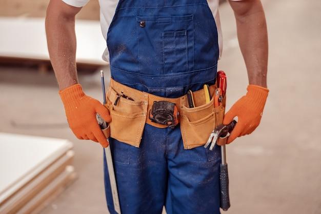 Lavoratore di sesso maschile che indossa una cintura degli attrezzi con strumenti da costruzione