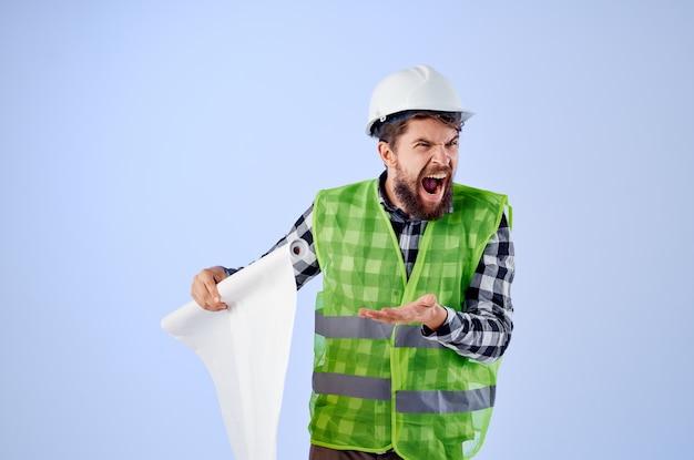 Un lavoratore di sesso maschile con un casco bianco disegna uno sfondo blu professionale