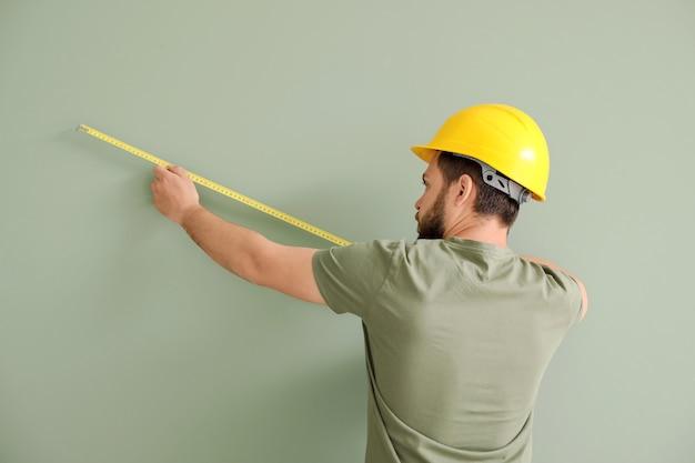 Lavoratore di sesso maschile con metro a nastro su grigio