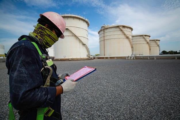 I lavori dei lavoratori maschi consentono l'ispezione visiva dell'industria della fila di grandi serbatoi bianchi per il cielo blu nuvoloso della stazione di servizio.