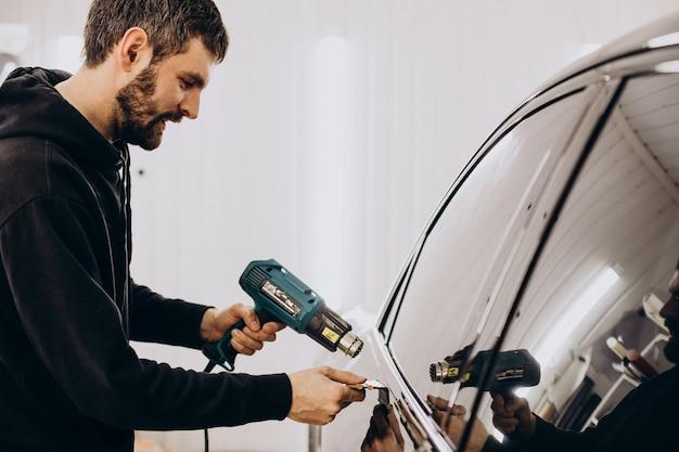 Operaio maschio che avvolge l'auto con pellicola protettiva