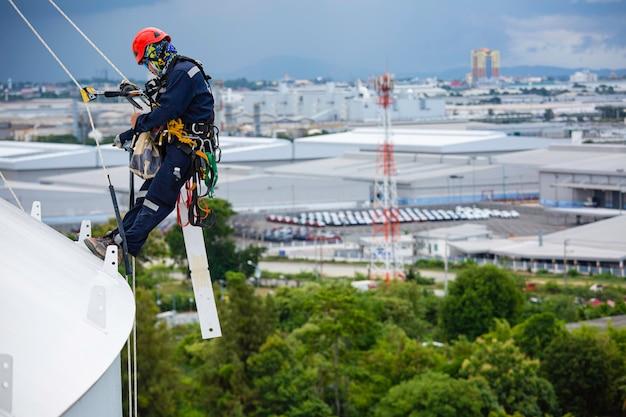 I lavoratori di sesso maschile controllano la fune verso il basso sul tetto del serbatoio superiore accesso alla fune ispezione dello spessore del serbatoio di stoccaggio della piastra del guscio lavori di sicurezza del gas in altezza.