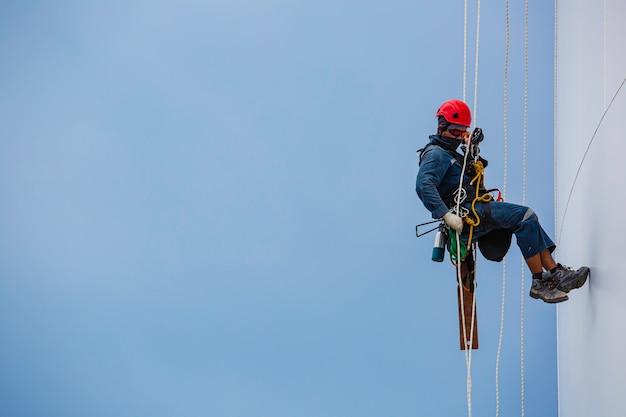 Lavoratori di sesso maschile in basso altezza serbatoio accesso fune ispezione di spessore lamiera serbatoio stoccaggio gas propano sicurezza lavori in quota.