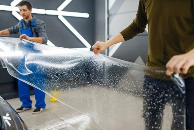 I lavoratori di sesso maschile tengono un modello di pellicola protettiva per auto trasparente. installazione di rivestimento che protegge la vernice dell'automobile dai graffi. veicolo nuovo in garage, procedura di messa a punto