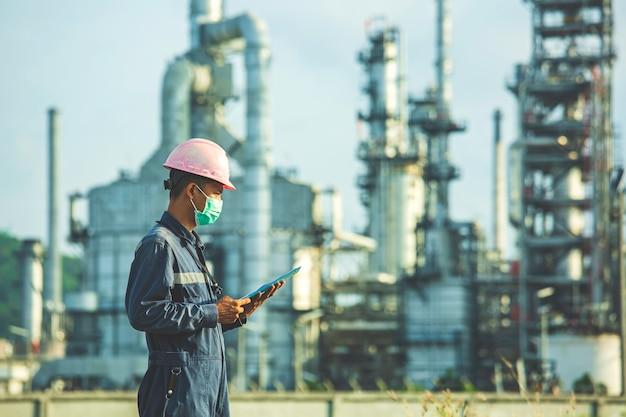 I lavoratori di sesso maschile eseguono ispezioni e registrano la raffineria di processo presso il cantiere industriale di petrolio e gas.