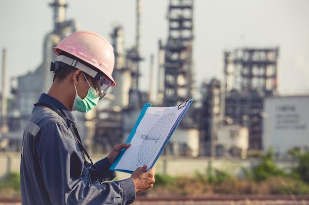 I lavoratori di sesso maschile eseguono ispezioni e registrano la raffineria di processo presso i cantieri industriali di petrolio e gas