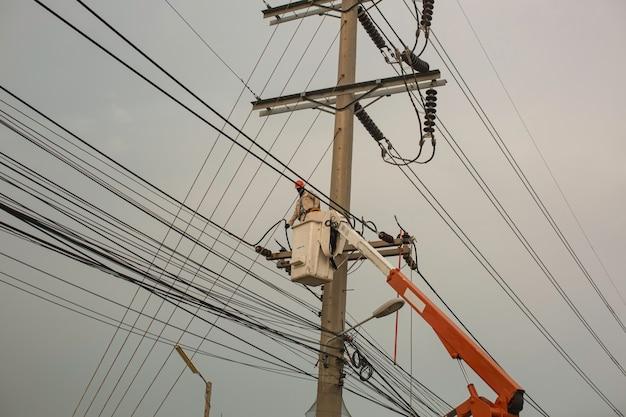 Lavoratori di sesso maschile installazione di pali elettrici di trasmissione ad alta tensione sulla gru per lavori in quota