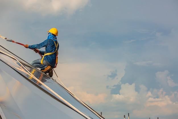 Sicurezza dell'altezza di accesso alla fune dei lavoratori di sesso maschile che si collega con un'imbracatura di sicurezza a nodo, si aggancia ai sistemi di punti di ancoraggio anticaduta e anticaduta del tetto pronti per la salita, cupola del serbatoio dell'olio da cantiere
