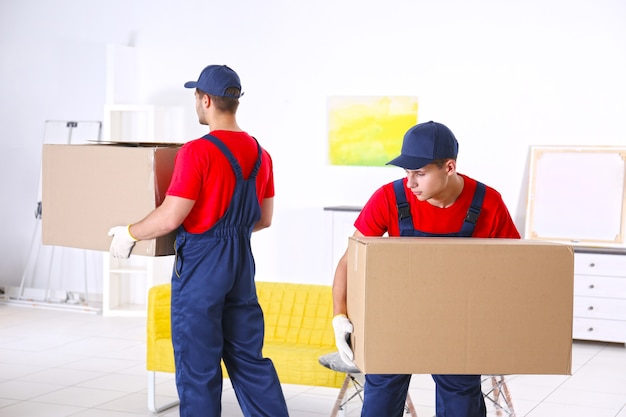 Lavoratori maschi con scatole e mobili nella nuova casa