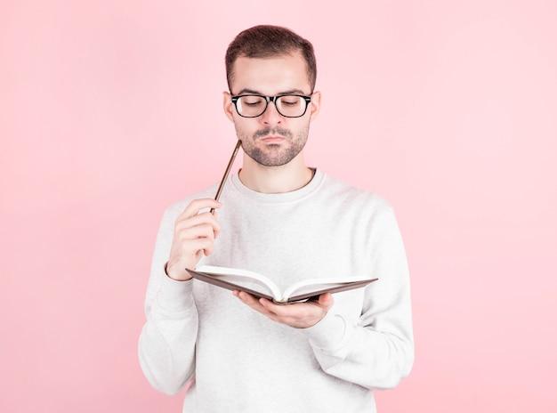Lo scrittore maschio con i capelli scuri con gli occhiali pensa a cosa scrivere in un libro, tiene una matita alla bocca, tiene un libro nell'altra mano. giornata internazionale degli scrittori