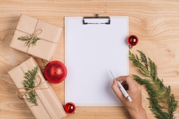 Maschio che scrive biglietto di auguri di natale e incarta i regali di natale. vista dall'alto con copia spazio