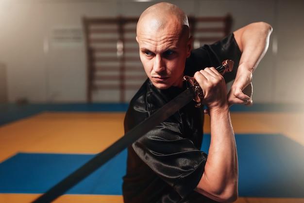 Maestro di wushu maschio con lama in azione, arti marziali. l'uomo in panno nero posa con la spada
