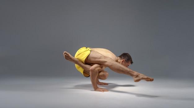 Yoga maschile in una posa difficile sulle mani, meditazione, muro grigio uomo forte che fa esercizio yogi, allenamento asana, massima concentrazione, stile di vita sano