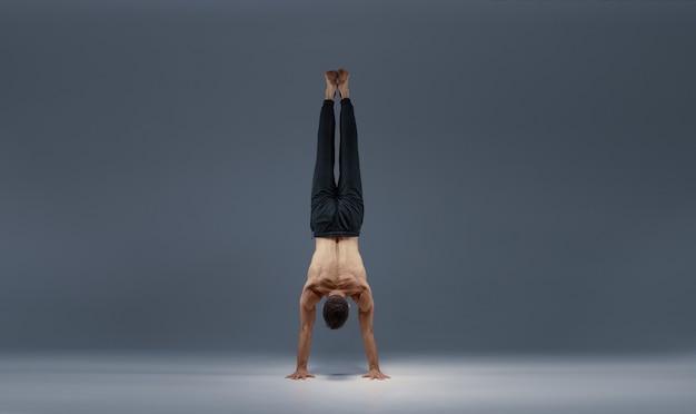 Lo yoga maschile si divide sulle mani, vista posteriore, muro grigio uomo forte che fa esercizio yogi, allenamento asana, massima concentrazione, stile di vita sano