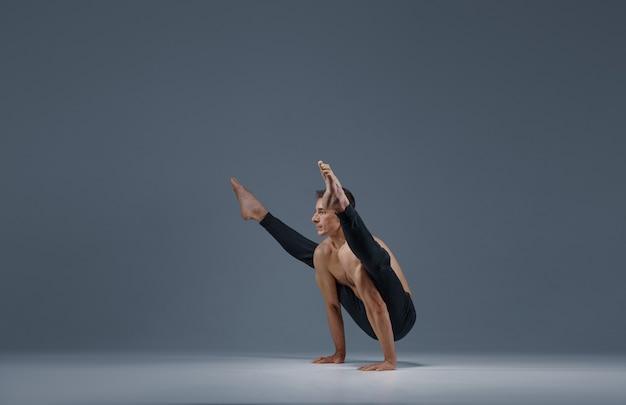 Yoga maschile fa spago diviso sulle mani, muro grigio uomo forte che fa esercizio yogi, allenamento asana, massima concentrazione, stile di vita sano