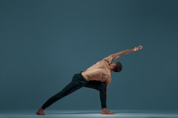 Yoga maschile facendo esercizio di stretching in studio, muro grigio uomo forte che pratica yogi, allenamento asana, massima concentrazione, stile di vita sano