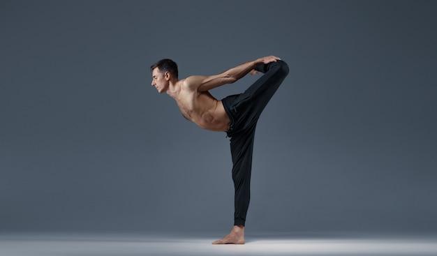 Lo yoga maschile mantiene l'equilibrio in una posa difficile, muro grigio uomo forte che fa esercizi yogi, allenamento asana, massima concentrazione, stile di vita sano