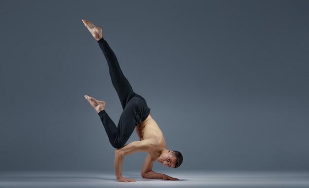 Lo yoga maschile mantiene l'equilibrio in una posa difficile sulle mani, muro grigio uomo forte che fa esercizio yogi, allenamento asana, massima concentrazione, stile di vita sano