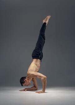 Lo yoga maschile mantiene l'equilibrio sulle mani, posizione di meditazione, muro grigio uomo forte che fa esercizi yogi, allenamento asana, massima concentrazione, stile di vita sano