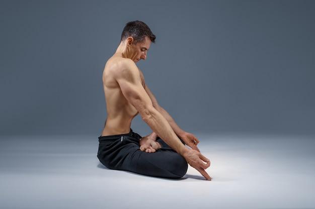 Yoga maschile madita in posa classica, posizione di meditazione, muro grigio uomo forte che fa esercizi yogi, allenamento asana, massima concentrazione, stile di vita sano