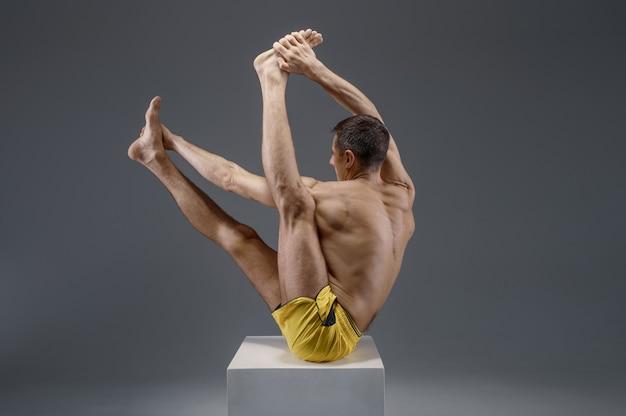 Yoga maschile seduto sul piedistallo in studio, posizione di meditazione, muro grigio uomo forte che fa esercizio yogi, allenamento asana, massima concentrazione, stile di vita sano