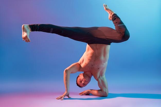 Yoga maschile in piedi sulle mani a testa in giù, indossa pantaloni neri, posa in topless