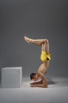 Yoga maschile in piedi sui gomiti, vista laterale, meditazione, muro grigio uomo forte che fa esercizio yogi, allenamento asana, massima concentrazione, stile di vita sano